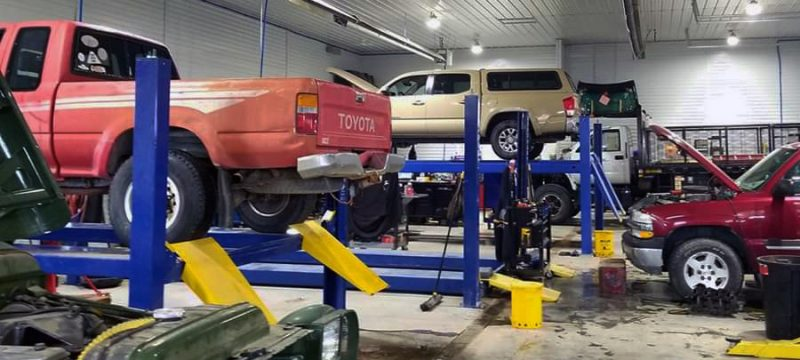 auto repair shop with cars on the lift